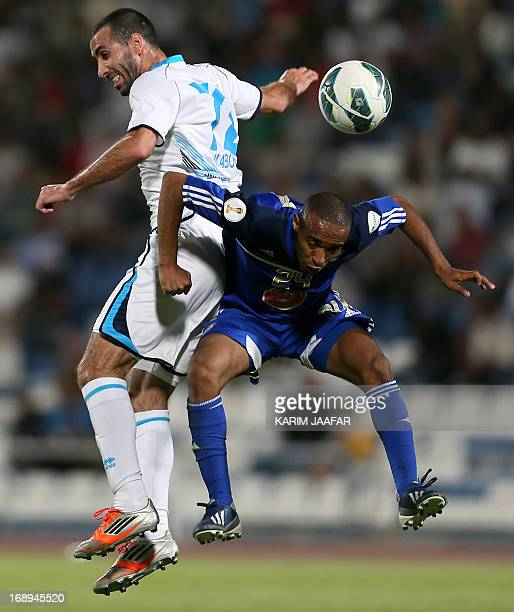 Baniyas' Egyptian striker Mohamed Aboutrika challenges AlKhor's Mohammed Jumaa during their GCC Champions League first leg final football match at...