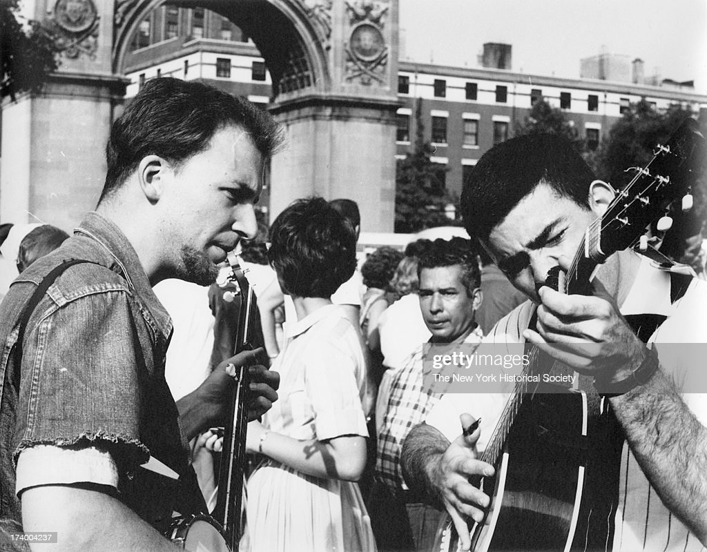 Banjo player and guitar player with crowds and Washington Square Arch in the background Washington Square Park New York New York August 26 1962