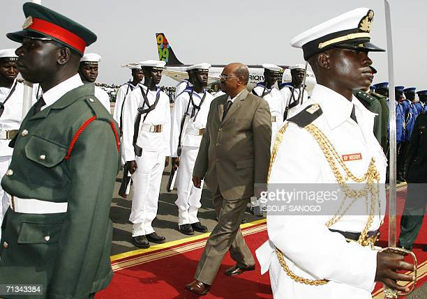 Sudanese President Omar alBeshir reviews an honour guard during a welcoming ceremony 30 June 2006 at Banjul airport on the eve of the biannual...