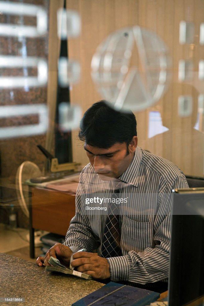 A Bank Alfalah Ltd. employee counts banknotes in one of the bank's branches in Karachi, Pakistan, on Wednesday, Oct. 17, 2012. Bank Alfalah, Pakistan's second-biggest Islamic lender, may see 20 percent growth in net income this year and in 2013 as it expands its branch network to tap growing demand for Shariah-compliant finance. Photographer: Asim Hafeez/Bloomberg via Getty Images