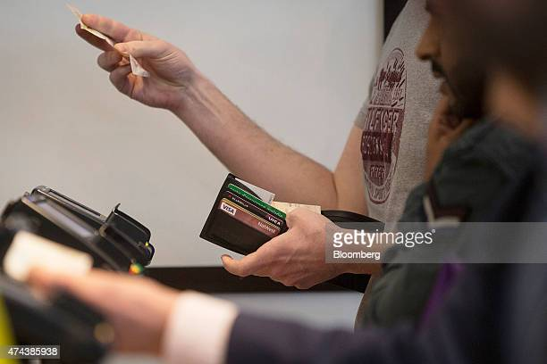 Bank and Visa Inc credit cards are seen in a man's wallet as he pays with cash using a British banknote at a restaurant in London UK on Friday May 22...