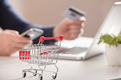 Online shopping. Bank card nearby a laptop and mini shopping cart on white background top view.