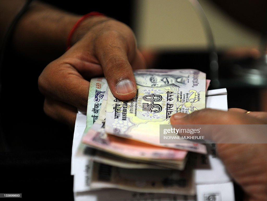a bank cashier receives n rupee not pictures getty images a bank cashier receives n rupee notes for a deposit from a customer in mumbai on