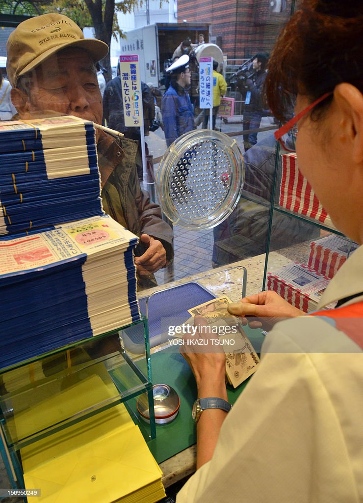 A bank clerk (R) counts bank notes as a customer purchases tickets for the 600 million yen (7.3 million USD) year-end Jumbo Lottery in Tokyo on November 26, 2012. Thousands of punters queued up for tickets in the hope of becoming a millionaire. AFP PHOTO / Yoshikazu TSUNO