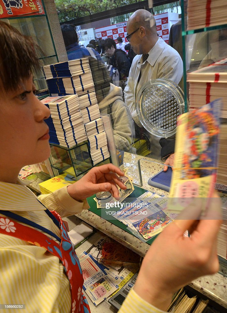 A bank clerk (L) prepares lottery tickets as customers queue for the 600 million yen (7.3 million USD) year-end Jumbo Lottery in Tokyo on November 26, 2012. Thousands of punters queued up for tickets in the hope of becoming a millionaire. AFP PHOTO / Yoshikazu TSUNO