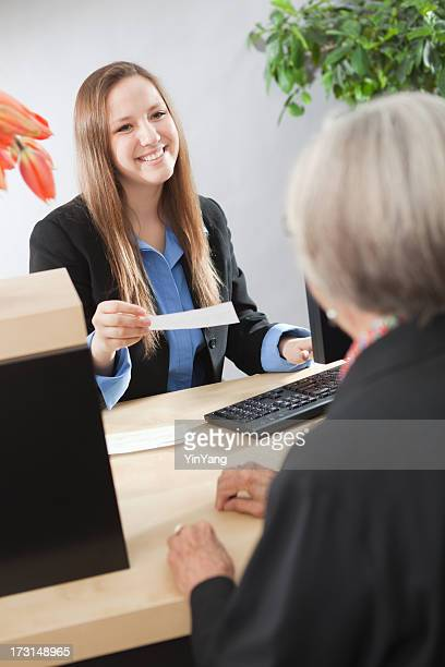 Bank Counter with Friendly Teller and Customer Making Transaction Vt