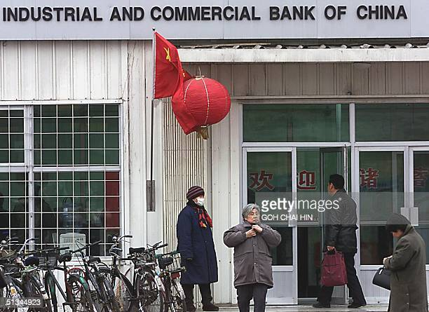 Bank customers make their way in and out of a bank in Beijing 03 January 2000 as Chinese banks opened for business as usual in the new year A small...