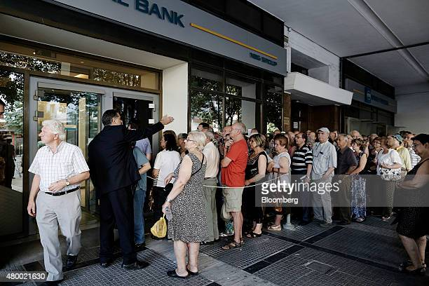 A bank employee arranges a queue of pensioners outside the entrance doors to a National Bank of Greece SA bank branch in Thessaloniki Greece on...