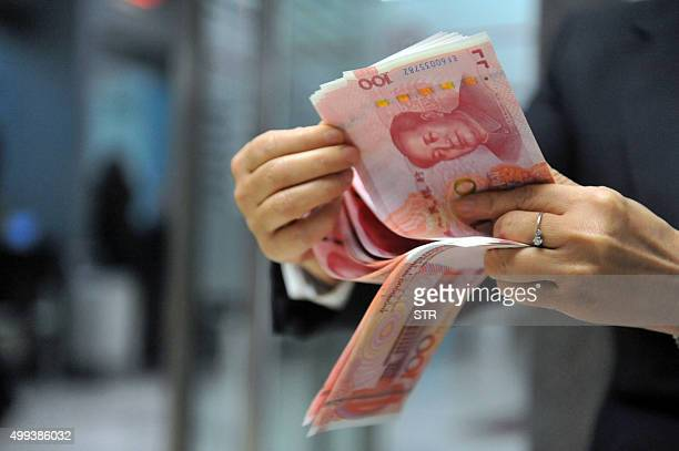 A bank employee counts 100yuan banknotes at a bank in Hangzhou east China's Zhejiang province on December 1 2015 The International Monetary Fund's...