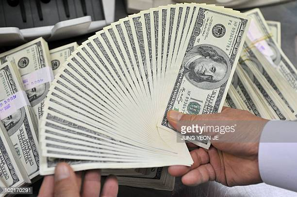 A bank employee counts US dollar bank notes at the Korean Exchange Bank in Seoul on October 30 2008 South Korea's parliament approved a plan to...