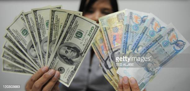 A bank employee displays US dollar and Philippine notes in Manila on August 3 2011Philippine President Benigno Aquino said August 3 the US dollar's...