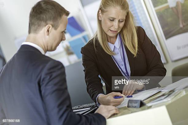 Bank employee explaining loan info to a customer