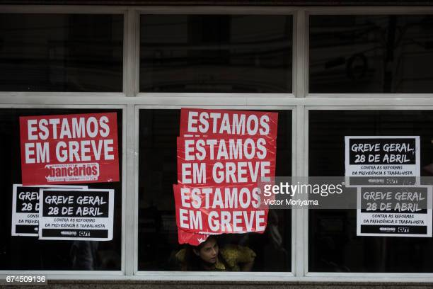 Bank employee observes the protest against the social welfare reform at the start of a nationwide strike called by unions opposing austerity reforms...