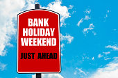 Bank Holiday Weekend Just Ahead motivational quote written on red road sign isolated over clear blue sky background. Concept  image with available copy space