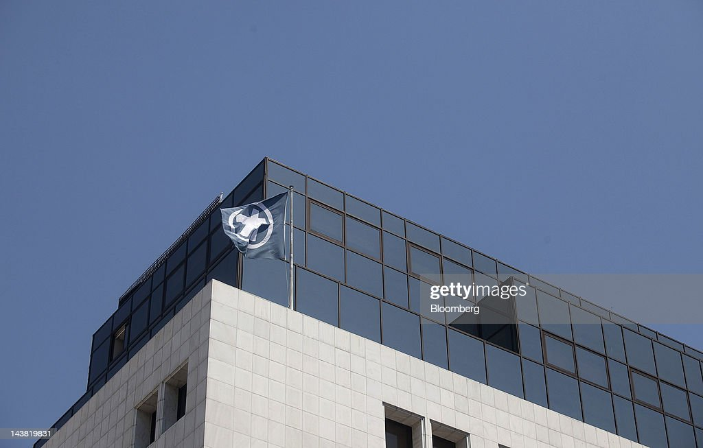 A bank logo is seen on a flag flying from the roof of the Alpha Bank AE headquarters in Athens, Greece, on Friday, May 4, 2012. European stocks dropped as investors awaited today's American payrolls report and elections in France, Greece, Italy and Germany this weekend. Photographer: Simon Dawson/Bloomberg via Getty Images