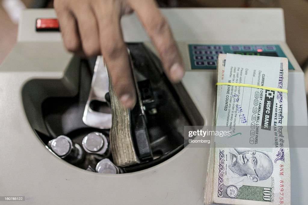 Bank Ltd. teller counts Indian 100 rupee banknotes at the company's bank branch in Mumbai, India, on Friday, Feb. 1, 2013. HDFC Bank, India's second-largest lender by market value, is seeking to expand in the rural market of the world's second-most populated nation to bolster profits as competition in its cities intensifies. Photographer: Dhiraj Singh/Bloomberg via Getty Images