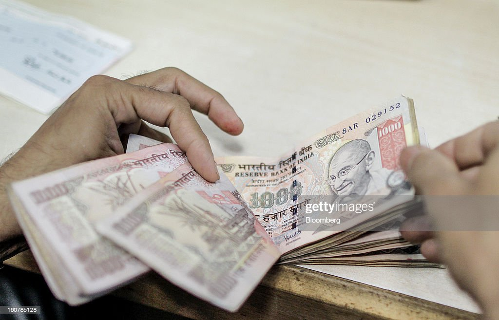 Bank Ltd. teller counts Indian 1000 rupee banknotes at the company's bank branch in Mumbai, India, on Friday, Feb. 1, 2013. HDFC Bank, India's second-largest lender by market value, is seeking to expand in the rural market of the world's second-most populated nation to bolster profits as competition in its cities intensifies. Photographer: Dhiraj Singh/Bloomberg via Getty Images