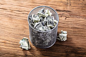 Elevated View Of Crumpled Bank Notes In Dustbin On Wooden Table