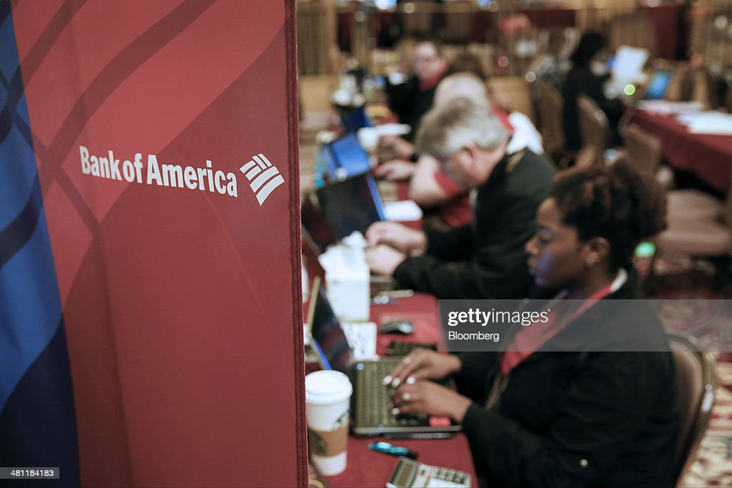 Bank of America Corp. signage is displayed as representatives work during the Neighborhood Assistance Corporation of America (NACA) event in Los Angeles, California, U.S., on Friday, March 28, 2014. Fed buying of the securities that helped spur a housing recovery is poised to fall below growth in the $5.5 trillion government-backed market as soon as May, Nomura Holdings Inc. said. Last year, the Fed added twice as much of the debt as was created, suppressing yields that guide mortgage interest rates. Photographer: Patrick T. Fallon/Bloomberg via Getty Images