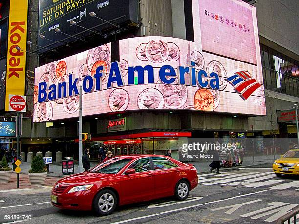 Bank of America on a background of falling dollar coins Electronic billboard in Times Square displaying money illustrating Keep the Change Bank of...