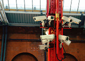 A bank of CCTV cameras in a train station.