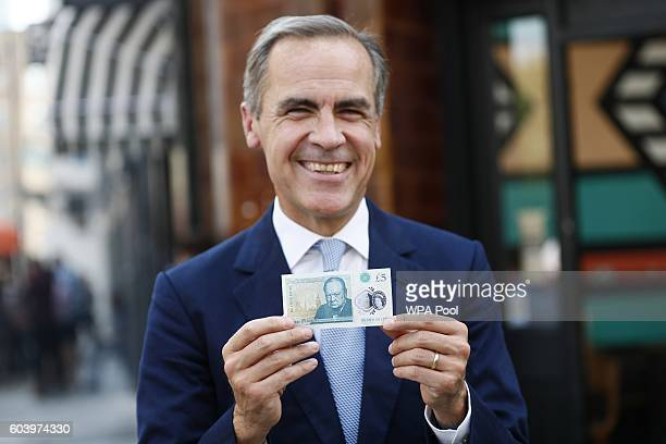 Bank of England governor Mark Carney poses with a new polymer five pound note at Whitecross Street Market on September 13 2016 in London United...