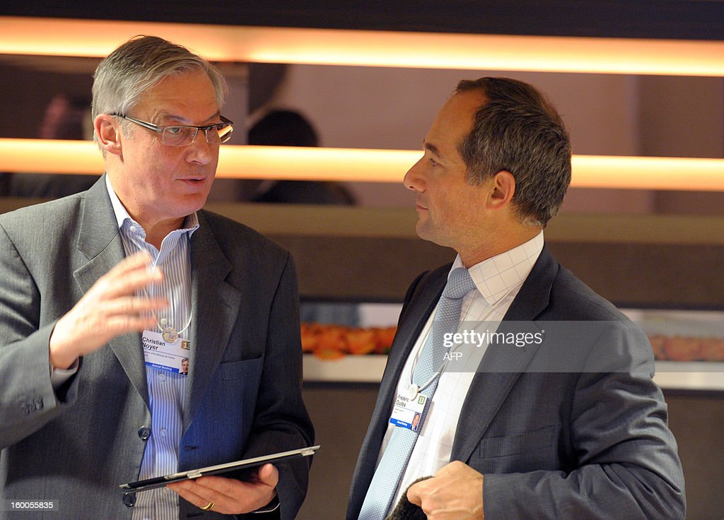 Bank of France Governor Christian Noyer (L) talks with tthe chief executive officer of French bank Societe Generale, Frederic Oudea, on January 25 at the World Economic Forum (WEF) in the Swiss resort of Davos. The WEF will see top politicians and business leaders pursue talks on whether they have seen the back of the global financial crisis. AFP PHOTO ERIC PIERMONT