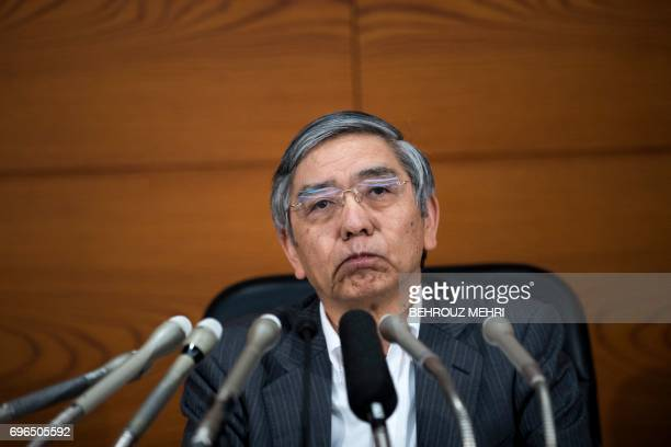 Bank of Japan governor Haruhiko Kuroda attends a press conference in Tokyo on June 16 2017 The Bank of Japan stood by its pledge to achieve moderate...