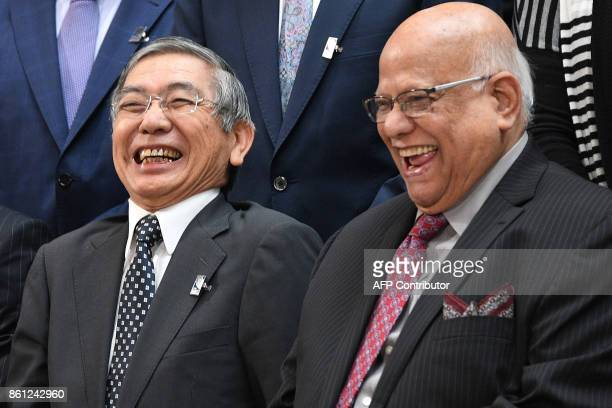 Bank of Japan Governor Haruhiko Kuroda laughs with an attending member during the family photo at the World Bank and International Monetary Fund...