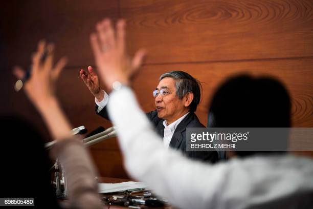 Bank of Japan governor Haruhiko Kuroda points at a journalist to ask a question during a press conference in Tokyo on June 16 2017 The Bank of Japan...