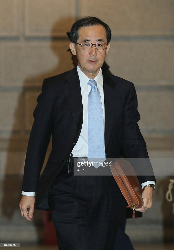 Bank of Japan (BOJ) Governor Masaaki Shirakawa enters the bank headquarters to attend a policy meeting in Tokyo on January 22, 2013. The BOJ wrapped up a two-day policy meeting with the under-pressure central bank widely expected to usher in fresh easing measures aimed at boosting the nation's limp economy. AFP PHOTO / JAPAN POOL via JIJI