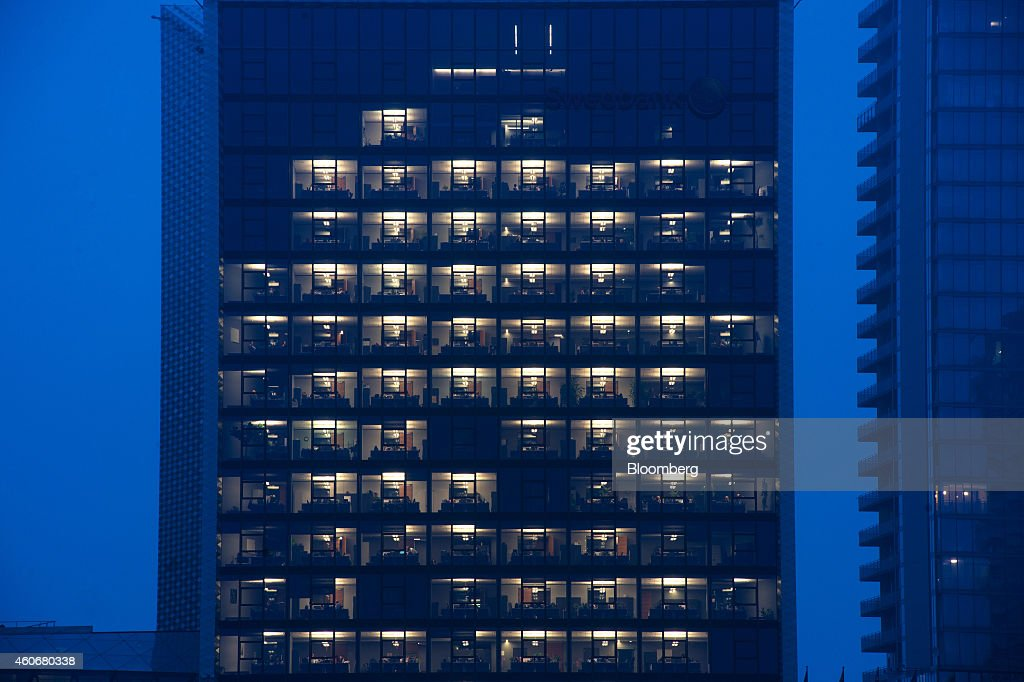 Bank offices sit illuminated at night in the Swedbank AB head office tower in Vilnius Lithuania on Monday Dec 15 2014 Lithuania will switch...