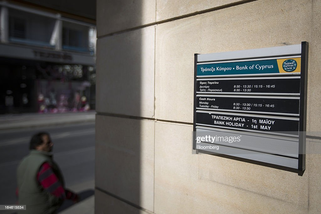 Bank opening times are displayed on a sign outside a closed Bank of Cyprus Plc branch in Nicosia, Cyprus, on Monday, March 25, 2013. Cyprus dodged a disorderly default and unprecedented exit from the euro by bowing to demands from creditors to shrink its banking system in exchange for 10 billion euros ($13 billion) of aid. Photographer: Simon Dawson/Bloomberg via Getty Images