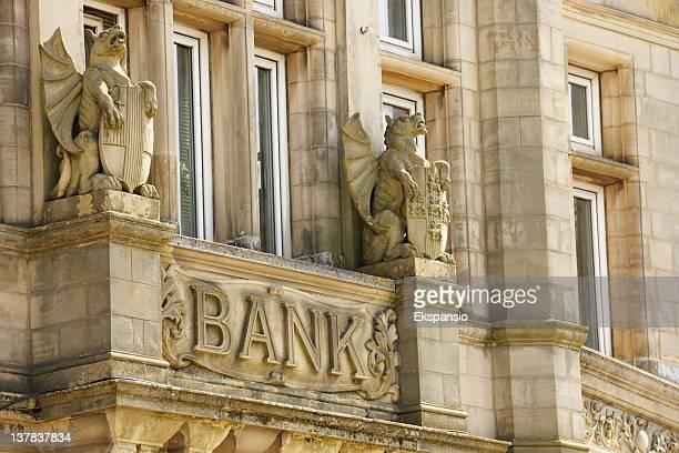 Bank-Schild auf alten Gebäude durch Stone Gryphons