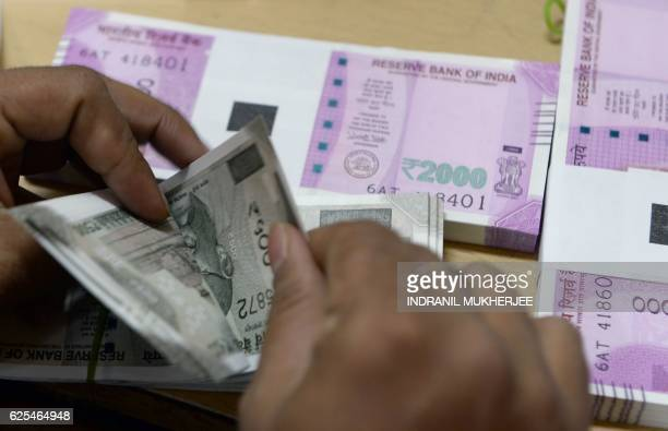 A bank staff member counts Indian 500 rupee notes to give to customers on November 24 in the wake of the demonetisation of old 500 and 1000 rupee...
