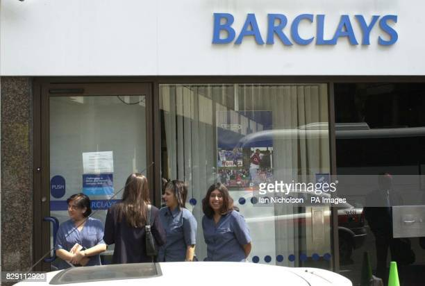 Bank staff stand outside their locked branch following a robbery just a stone's throw from police headquarters at Scotland Yard A pair of bank...