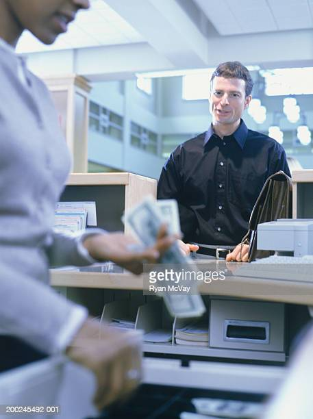 Bank teller and man at reception desk