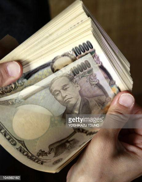 A bank teller counts 10000 yen bank notes in Tokyo on September 22 2010 The USD tumbled against the yen in Asia after the US Federal Reserve...