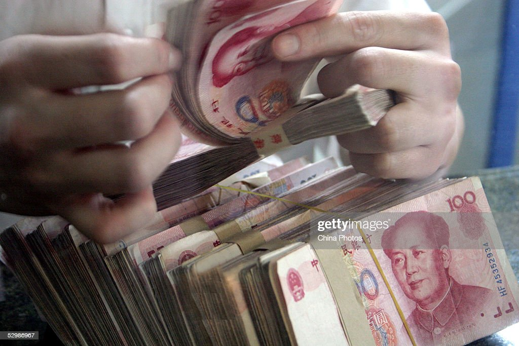 A bank teller counts Chinese currency 100 yuan (or Renminbi) notes on May 26, 2005 in Chengdu of Sichuan Province, China. China is under fierce pressure to free up the yuan, particularly from the United States. China's central bank, the People's Bank of China said in its first quarter report that China will keep its currency stable at a 'reasonable and well-balanced level' while improving the yuan's exchange rate mechanism.
