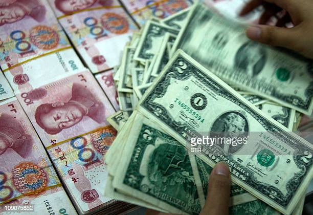 A bank teller counts stacks of US dollars and Chinese yuan at a bank in Huaibei central China's Anhui province on November 4 2010 Unrestricted...
