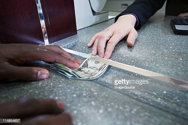 Bank teller giving cash to customer