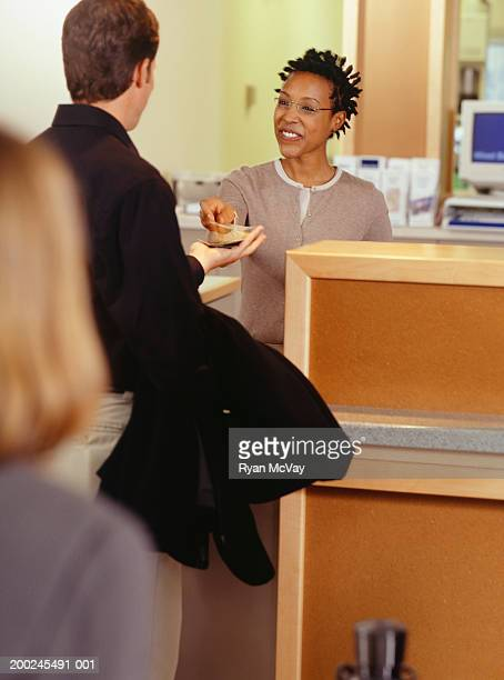 Bank teller giving customer money