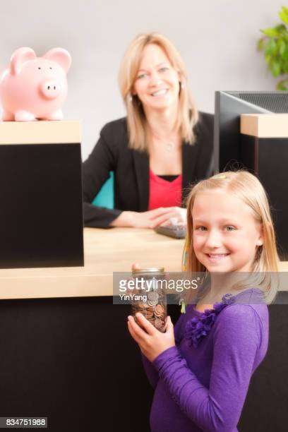 Bank Teller Serving Young Girl Children Customers with Saving at Retail Bank Counter