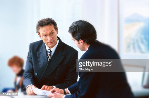 A bank teller talking with a customer : Stock Photo