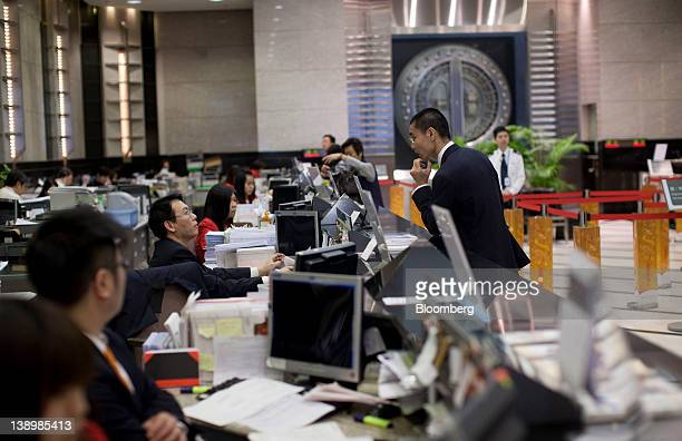 Bank tellers serve customers in the Bank of East Asia Ltd main branch in Hong Kong China on Wednesday Feb 15 2012 Bank of East Asia Hong Kong's...