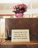 Bank  transaction sign on counter, potted flower on top