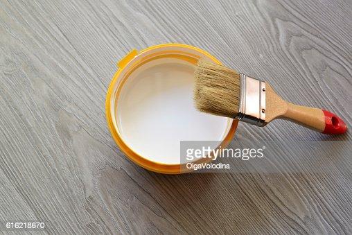 Bank mit weißer Farbe und Pinsel auf Etage : Stock-Foto