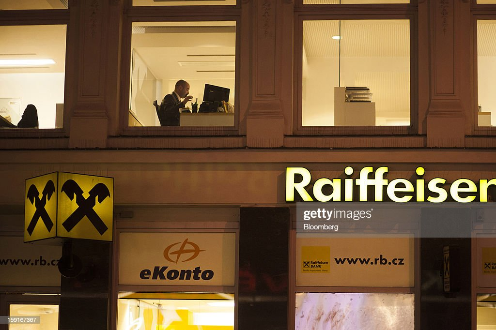 A bank worker is seen at work through the window of a Raiffeisen Bank International AG branch in Prague, Czech Republic, on Tuesday, Jan. 8, 2013. The Czech economy is showing weak domestic demand as households and businesses cut spending due to government austerity programs and the euro area's debt crisis. Photographer: Bartek Sadowski/Bloomberg via Getty Images