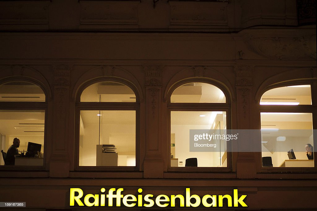 Bank workers are seen at work through the windows of a Raiffeisen Bank International AG branch in Prague, Czech Republic, on Tuesday, Jan. 8, 2013. The Czech economy is showing weak domestic demand as households and businesses cut spending due to government austerity programs and the euro area's debt crisis. Photographer: Bartek Sadowski/Bloomberg via Getty Images