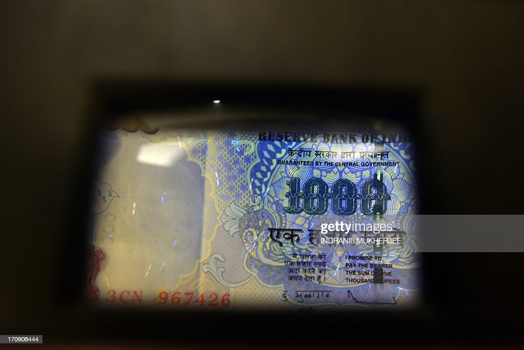 A banker inspects a 1,000 rupee currency note through a magnifier equipped with an ultraviolet light source, used to detect fake notes, in Mumbai on June 20, 2013. India's rupee hit a new record low against the dollar June 20, on concerns the US Federal Reserve would scale back its stimulus programme that has pumped billions of dollars into global markets. The rupee hit 59.93 in morning trade, well below its previous record low of 58.98 reached last week, prompting the Indian government to move to allay investor concerns over the currency. AFP PHOTO/ Indranil MUKHERJEE
